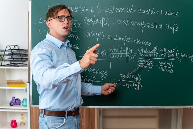 Giovane insegnante maschio con gli occhiali che tiene il puntatore che spiega la lezione guardando fiducioso in piedi vicino alla lavagna con formule matematiche in classe