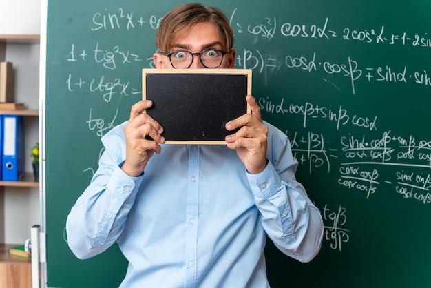 Giovane insegnante maschio con gli occhiali che tiene una piccola lavagna davanti al viso che sembra sorpreso in piedi vicino alla lavagna con formule matematiche in classe