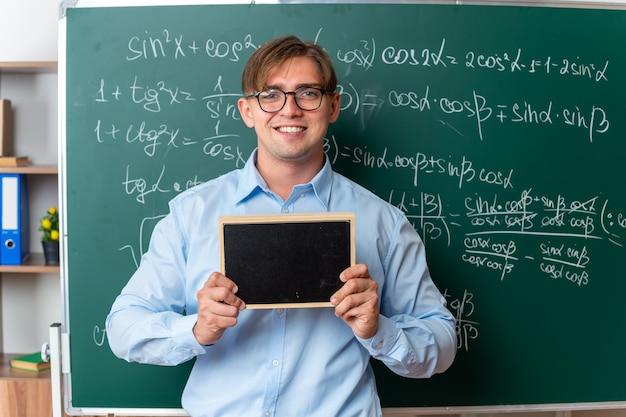 Giovane insegnante maschio con gli occhiali che tiene una piccola lavagna che sembra sorridente fiducioso in piedi vicino alla lavagna con formule matematiche in classe