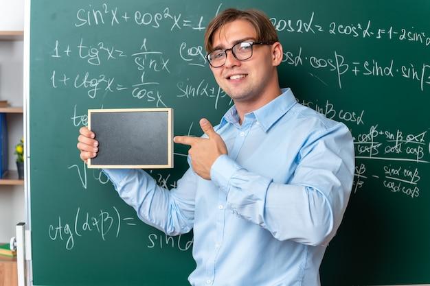 Giovane insegnante maschio con gli occhiali che tiene una piccola lavagna puntata con il dito indice su di essa sorridente fiducioso in piedi vicino alla lavagna con formule matematiche in classe
