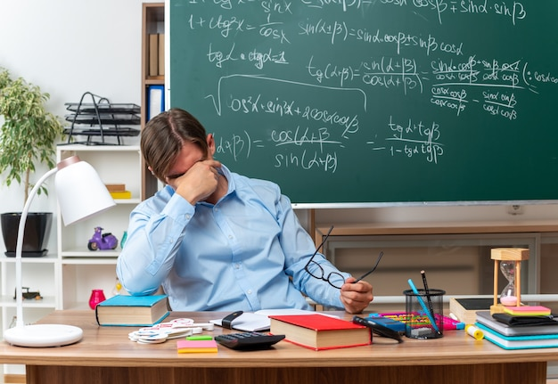 Young male teacher wearing glasses loking tired and overworked covering eyes with hand sitting at school desk with books and notes in front of blackboard in classroom