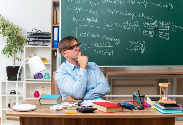 Young male teacher wearing glasses looking aside with hand on chin with pensive expression thinking sitting at school desk with books and notes in front of blackboard in classroom