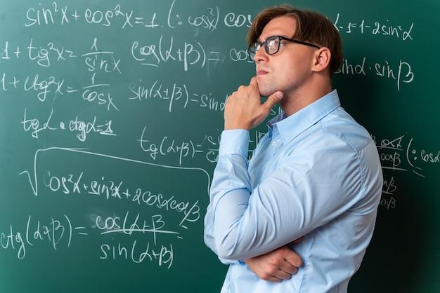 Giovane insegnante maschio con gli occhiali che guarda da parte con la mano vicino al mento con espressione pensosa pensando in piedi vicino alla lavagna con formule matematiche in classe