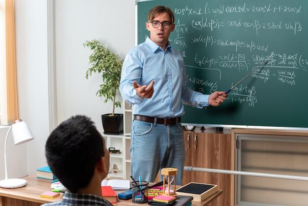 Молодой учитель-мужчина в очках выглядит смущенным и недовольным, объясняя урок ученикам, стоя возле доски с математическими формулами в классе