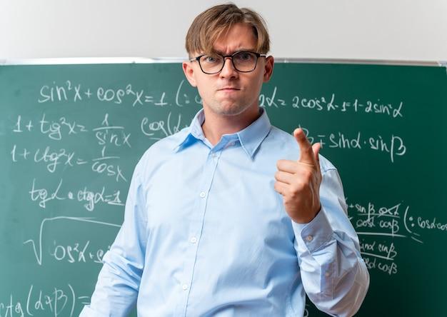 Giovane insegnante maschio con gli occhiali che sembra dispiaciuto e arrabbiato in piedi vicino alla lavagna con formule matematiche in classe