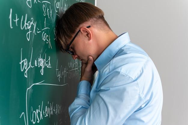 Giovane insegnante maschio con gli occhiali che sembra perplesso senza risposta in piedi vicino alla lavagna con formule matematiche in classe