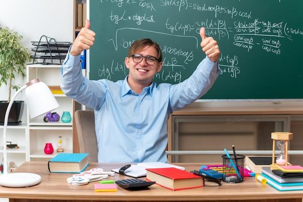 안경을 쓰고 젊은 남성 교사가 교실에서 칠판 앞에 책과 메모와 함께 학교 책상에 앉아 엄지 손가락을 유쾌하게 보여주는 미소를 찾고 있습니다.