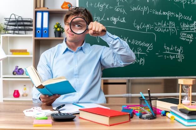 Giovane insegnante maschio con gli occhiali guardando attraverso la lente di ingrandimento seduto al banco di scuola con libri e note davanti alla lavagna in classe