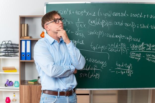 Giovane insegnante maschio con gli occhiali che guarda perplesso in piedi vicino alla lavagna con formule matematiche in classe