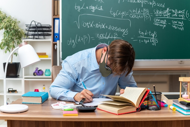 Young male teacher wearing glasses and protective facial mask writing preparing lesson sitting at school desk with books and notes in front of blackboard in classroom