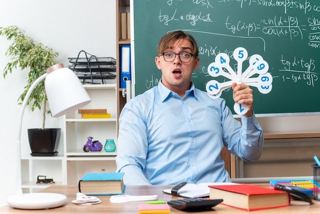 Giovane insegnante maschio con gli occhiali che mostra le targhe che spiegano la lezione guardando sorpreso seduto al banco di scuola con libri e note davanti alla lavagna in aula