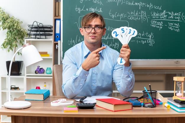 수업을 설명하는 번호판을 보여주는 안경을 착용하는 젊은 남성 교사는 교실에서 칠판 앞에 책과 메모와 함께 학교 책상에 앉아보고 웃고