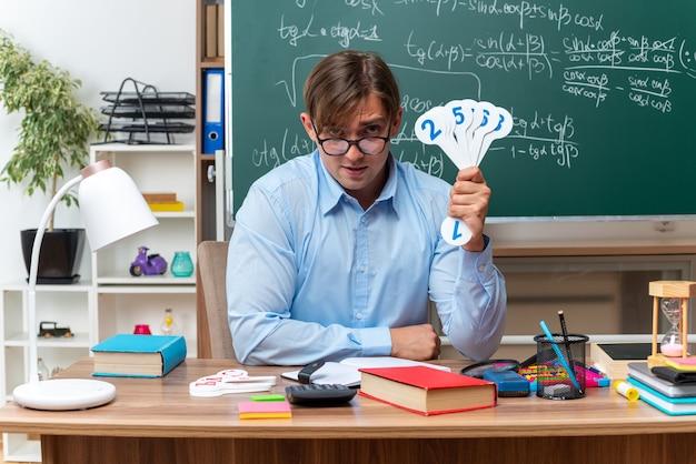 Giovane insegnante maschio che indossa occhiali che mostrano targhe che spiegano la lezione sorridente seduto al banco di scuola con libri e note davanti alla lavagna in classe