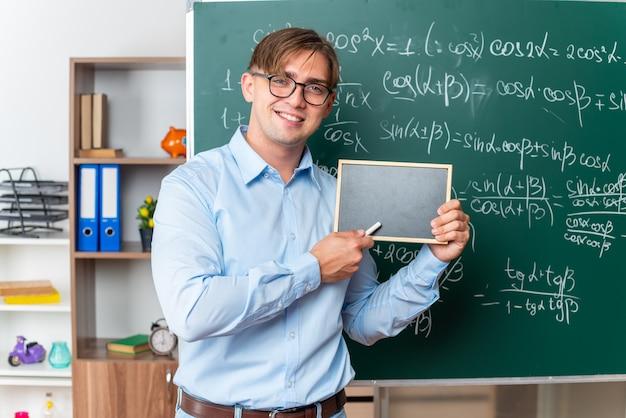 Giovane insegnante maschio con gli occhiali che mostra una piccola lavagna sorridente fiducioso in piedi vicino alla lavagna con formule matematiche in classe