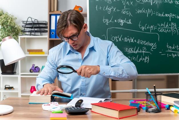 Молодой учитель-мужчина в очках сидит за школьной партой с книгами и заметками, глядя через увеличительное стекло на книгу перед доской в классе