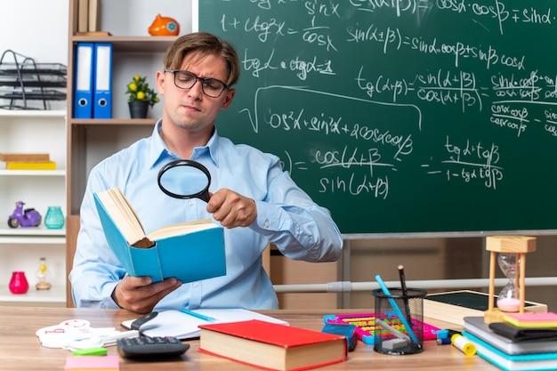 교실에서 칠판 앞에 심각한 얼굴로 책에 돋보기를 통해 찾고 책과 노트와 학교 책상에 앉아 안경을 착용하는 젊은 남성 교사