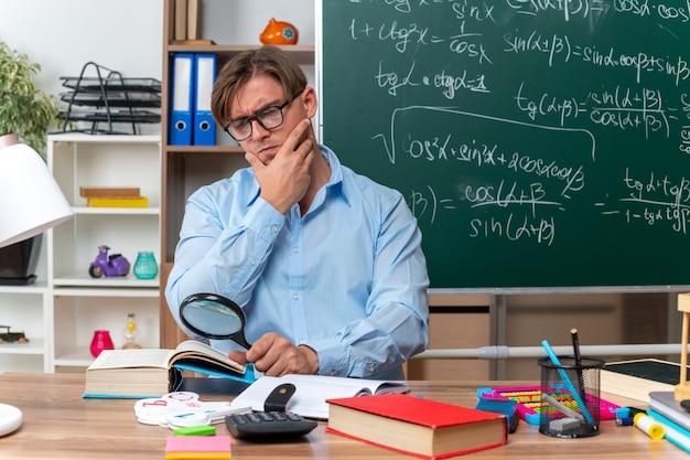 Молодой учитель-мужчина в очках сидит за школьной партой с книгами и заметками, глядя через увеличительное стекло на книгу с серьезным лицом перед доской в классе
