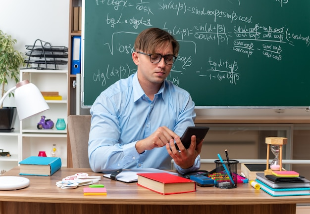 Young male teacher wearing glasses typing message using smartphone looking confident sitting at school desk with books and notes in front of blackboard in classroom