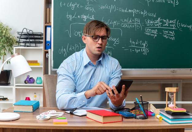 Giovane insegnante maschio con gli occhiali che digita un messaggio utilizzando lo smartphone che sembra sicuro seduto al banco di scuola con libri e note davanti alla lavagna in classe in