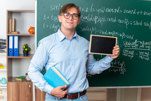 Giovane insegnante maschio che indossa occhiali con libro che tiene piccola lavagna sorridente fiducioso in piedi vicino alla lavagna con formule matematiche in classe