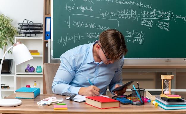 Giovane insegnante maschio con gli occhiali con la calcolatrice che prepara la lezione guardando fiducioso seduto al banco di scuola con libri e note davanti alla lavagna in classe