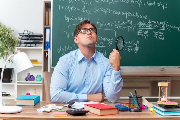Молодой учитель-мужчина в очках с увеличительным стеклом готовит урок, озадаченный глядя вверх, сидя за школьной партой с книгами и заметками перед доской в классе