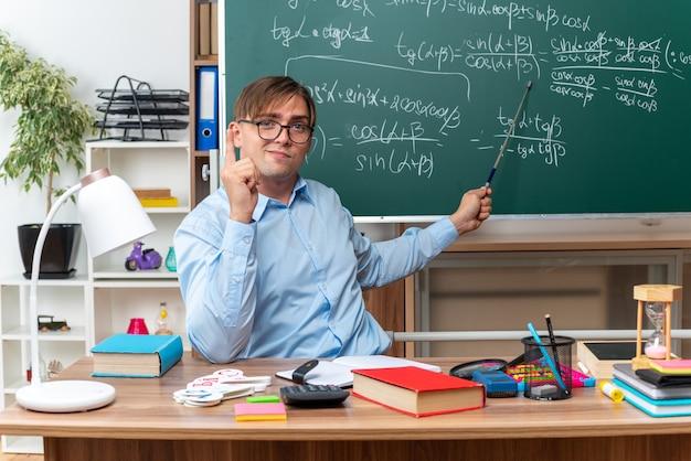 Giovane insegnante maschio con gli occhiali con puntatore che spiega la lezione guardando fiducioso seduto al banco di scuola con libri e note davanti alla lavagna in aula