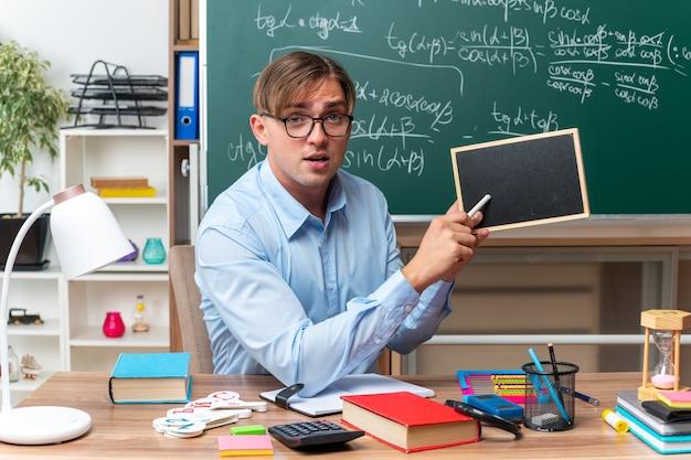 Giovane insegnante maschio con gli occhiali con una piccola lavagna e un pezzo di gesso che spiega la lezione guardando fiducioso seduto al banco di scuola con libri e note davanti alla lavagna in aula
