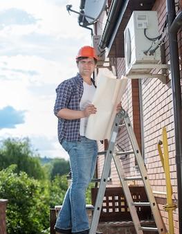 Молодой мужской техник, проверяющий систему кондиционирования воздуха с инструкциями