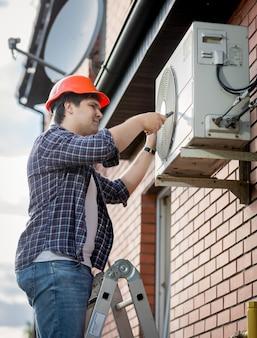 Молодой мужской техник, ремонтирующий наружную систему кондиционирования воздуха