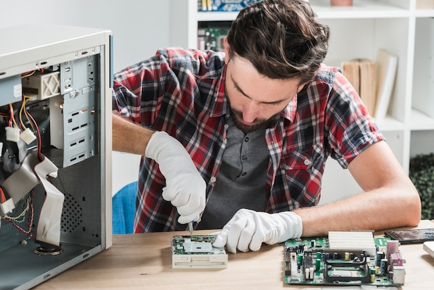 Young male technician wearing gloves fixing computer motherboard with screwdriver