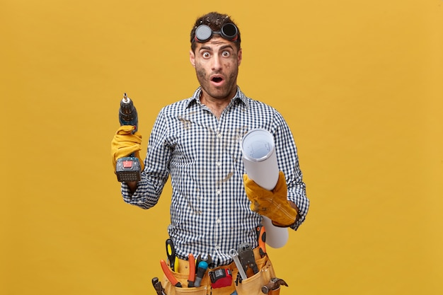 Молодой техник-мужчина с грязным лицом в защитных перчатках держит в руках сверлильный станок и чертеж с шокированным выражением лица, понимающим, сколько ему нужно сделать