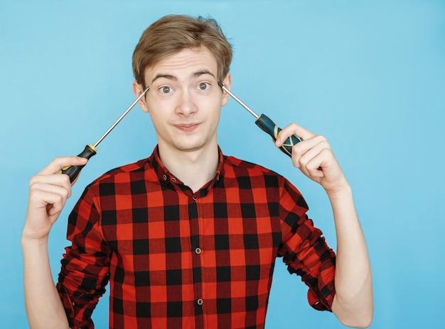 青い背景の上の赤いシャツの若い男性のティーンエイジャー