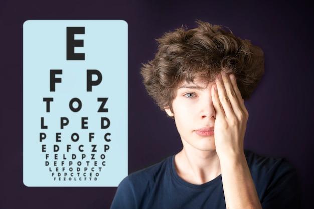 若い男性は目の視力をテストし、手で目を覆いますb
