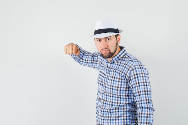 체크 셔츠, 모자에 주먹으로 위협하고 분노한 젊은 남성. 전면보기.