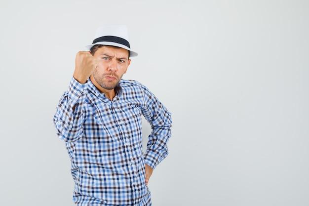 체크 셔츠에 주먹으로 위협하는 젊은 남성