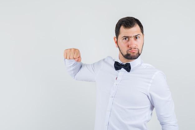 흰 셔츠에 주먹으로 위협하고 분노를 찾고 젊은 남성. 전면보기.