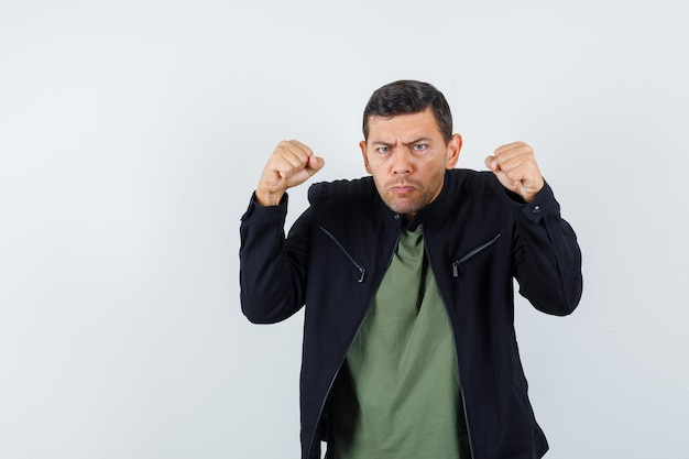 Молодой мужчина угрожает кулаками в футболке, куртке и выглядит сердитым. передний план.