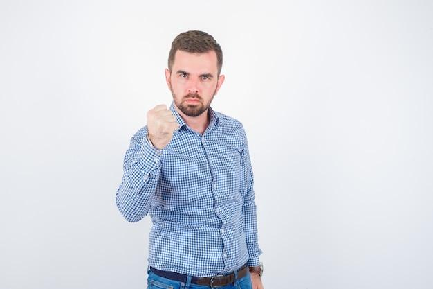 シャツの拳で脅し、真剣に見える若い男性、正面図。