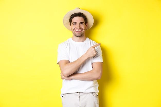Giovane turista maschio che punta il dito a destra, sorride e mostra pubblicità, concetto di turismo e stile di vita, sfondo giallo
