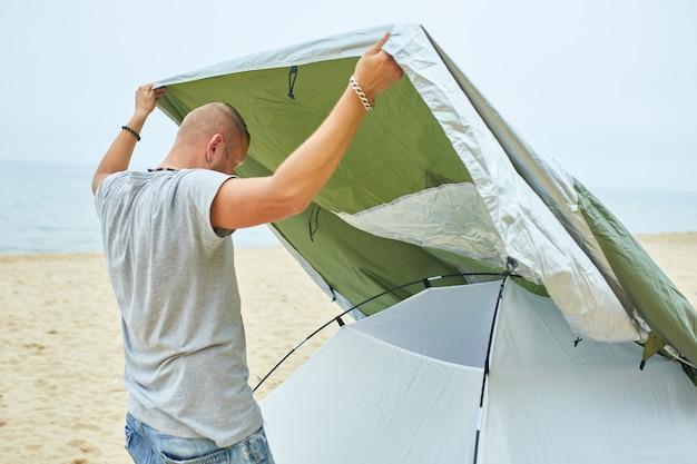 若い男性の観光客は、ビーチの海岸に緑のテントを置きます。男はハイキングでキャンプを設定し、一人でテントを集め、新しい通常の旅行をします。