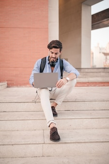 Young male tourist sitting on staircase using laptop