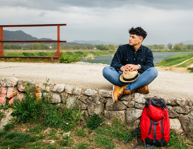Молодой мужчина турист сидит с рюкзаком возле красивой реки