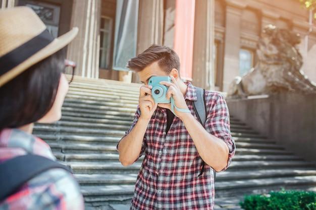 Молодой мужчина турист стоит на ступеньках и фотографирует женщину