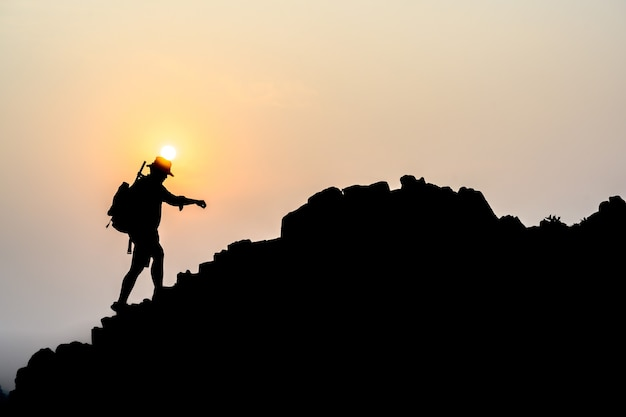 Young male tourists climbing mountains ideas for personal development and goals in the life of a climber with a backpack.
