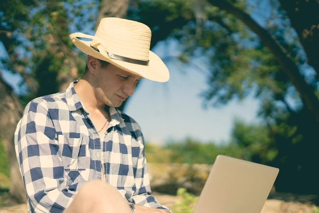 ビーチでラポップで働く若い男性旅行グラフィックデザイナーフリーランサー