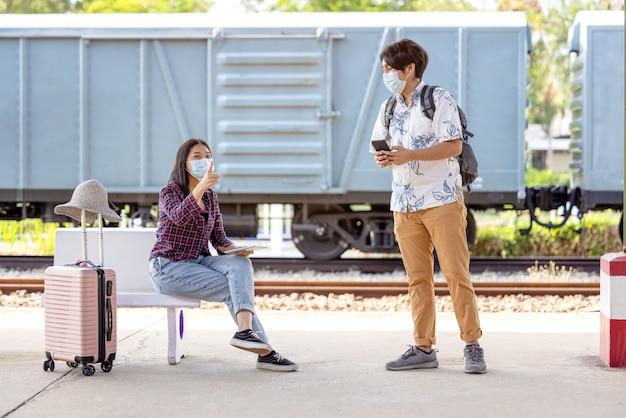 마스크와 모바일 젊은 남성 여행자 배낭 손에 앉아 지하철에서 계단을 가리키는 여성의 도움을 요청하는 방법, covid 거리