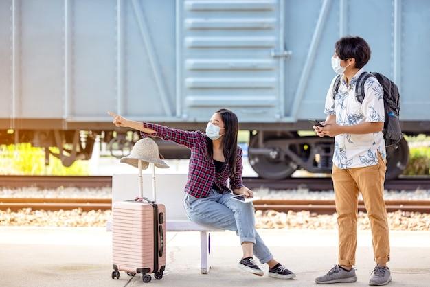 マスクと携帯電話を手にした若い男性の旅行者用バックパックは、地下鉄の階段に座って指さしている女性に助けを求めています。