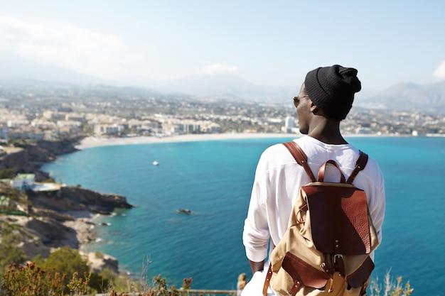 広大な紺碧の海と岩だらけの海岸を眺めながら革のバックパックを運ぶ若い男性旅行者