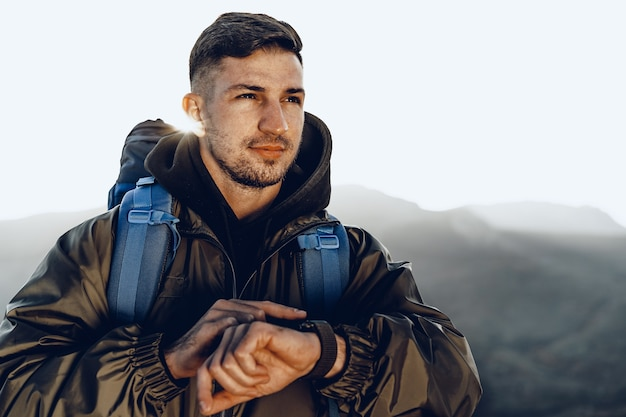 Young male traveler looking at his smart watch